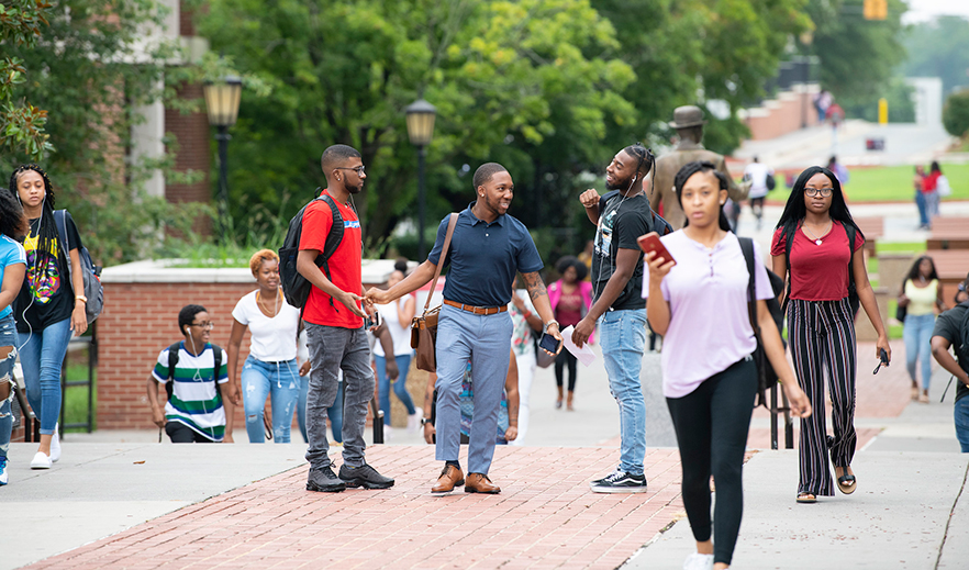 students walk near the S.G. Atkins statue on campus