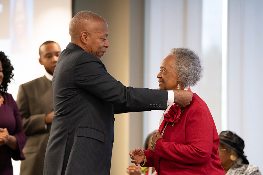 Chancellor Robinson places medallion around neck of honoree