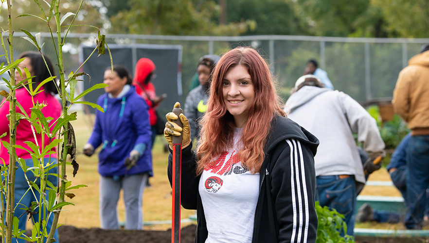 Miranda stands with a shovel in the community garden