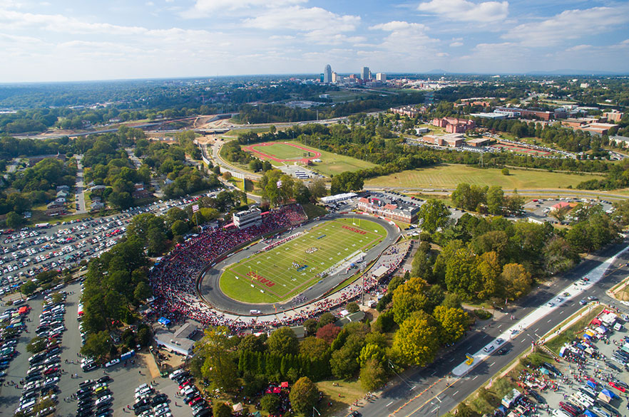 Aerial photo of Bowman Gray Stadium with city's downtown skyline in the background.
