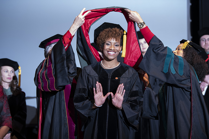 student forms a W with her hands as she receives her doctoral hood