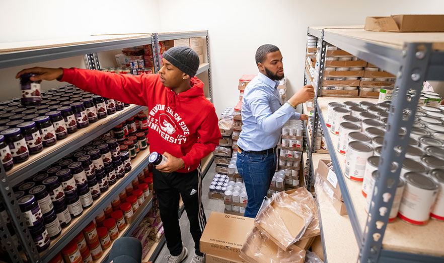 2 students restock shelves at food pantry