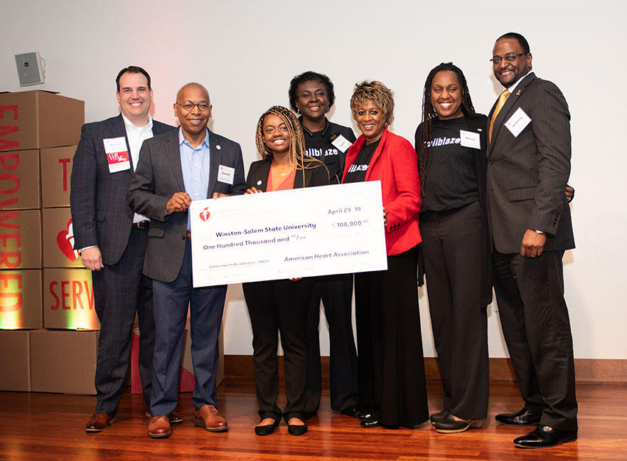 Group stands with large check for presentation of $100,000 grant