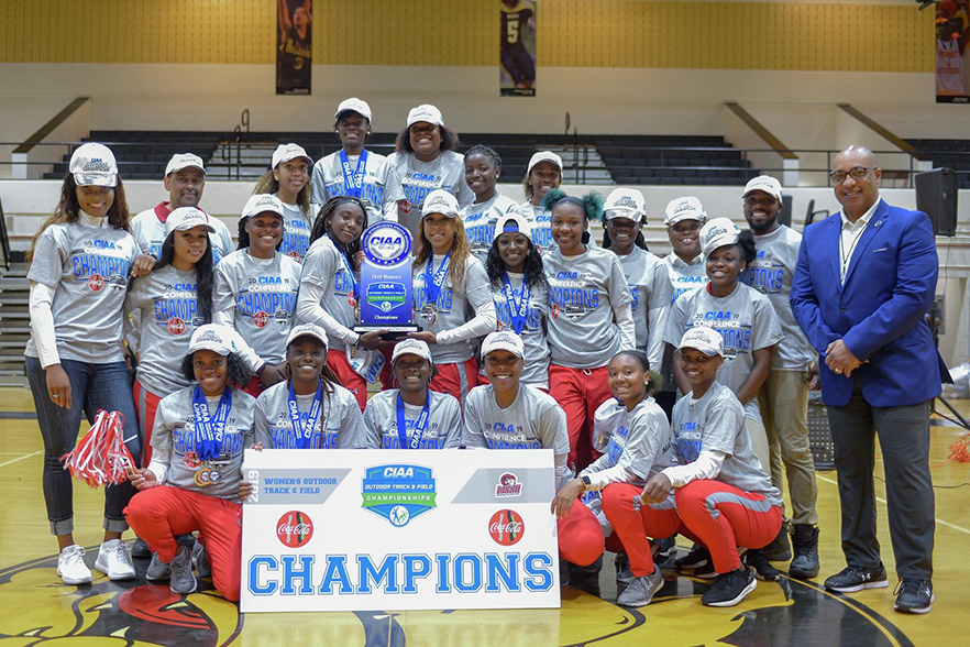 Track team stands with trophy and banner